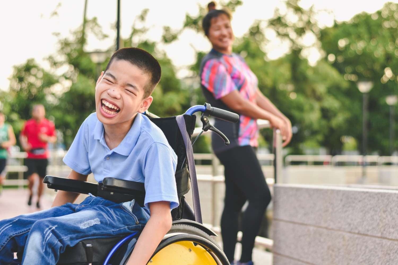 Jeune garçon souriant dans son fauteuil roulant