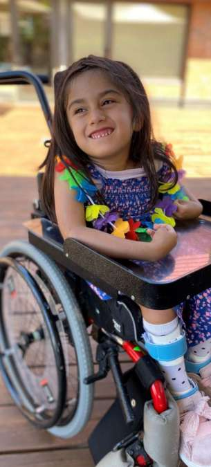 Petite fille souriante en fauteuil roulant